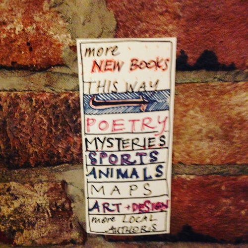 more new books sign brick wall